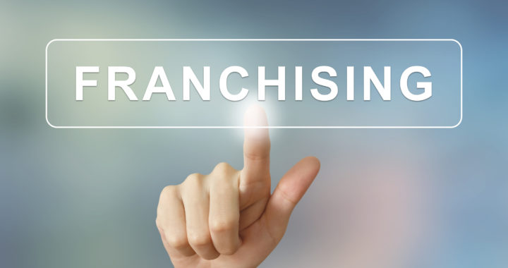 business hand pushing franchising button on blurred background